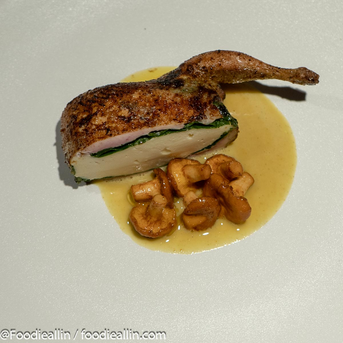 Roasted quail stuffed with quail mousse and spinach, served with girolles and curry.
